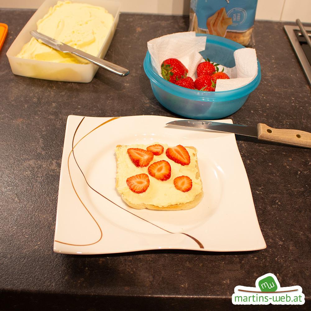 Creme aufstreichen und Erdbeeren klein schneiden
